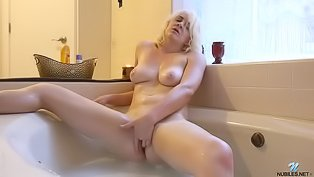 Blonde is having solo in bathtub