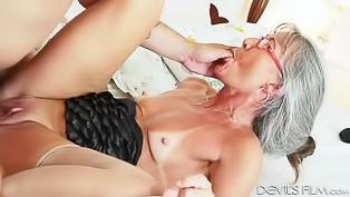 Tanned old woman rides a young cock